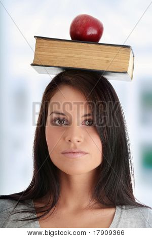 Beautiful student woman have book and one apple on her head - learning concept