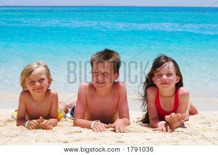 Drei Kinder, die am Strand liegen
