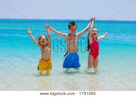 Three Children Wading In Ocean