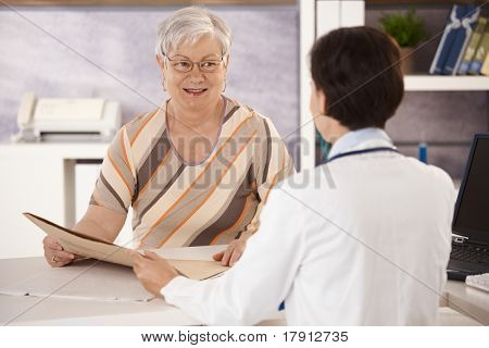 Female pensioner at doctors office listening to doctors explanation.?