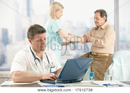Medical checkup in doctor's office, doctor working with laptop, nurse in background measuring patient blood pressure.?
