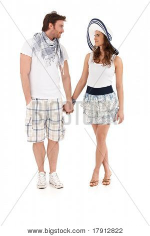 Young couple in summer outfit walking hand in hand, looking at each other, smiling, isolated on white background.?