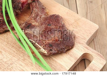 served main course: grilled pork ribs served with green chives over wooden plate