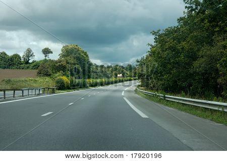 Verde paisaje se dividen por una autopista con un cielo amenazante