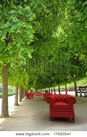 Red leather club sofas in a formal garden