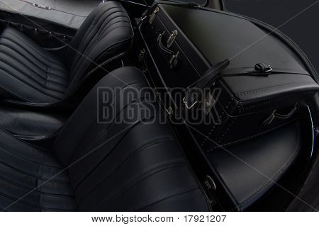 Backseat of a vintage car with retro luggage in the trunk