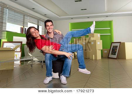 Young couple happy after moving in their new home. The images of the pictures are mine, and the label information is made up, so no copyright issue
