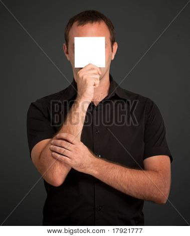 Man in black with a blank paper hiding his face