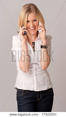 Young blond woman laughingly talking with two telephone receivers
