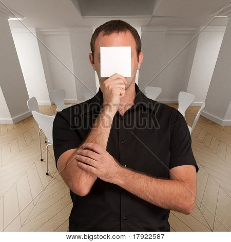 Man in black with a blank paper hiding his face in a meeting room
