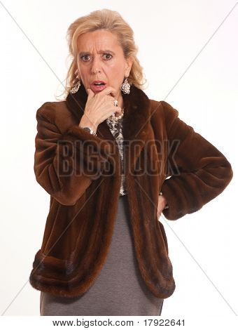 Portrait of a horrified elegant senior lady in a mink coat