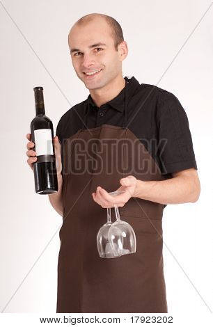 Man with apron presenting a wine bottle with a blank lable