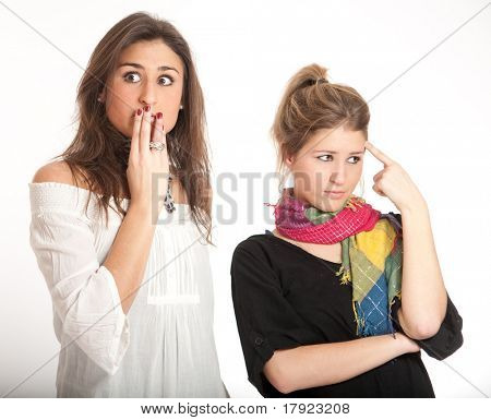 Two young girls, a blonde and a brunette, with a shocked expression