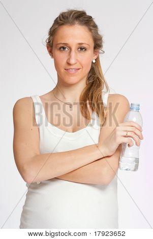 Junge schwangere Frau hält eine Flasche Wasser