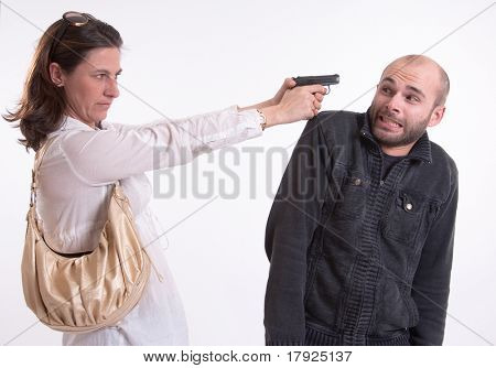 Dangerous woman pointing her gun to a scared man