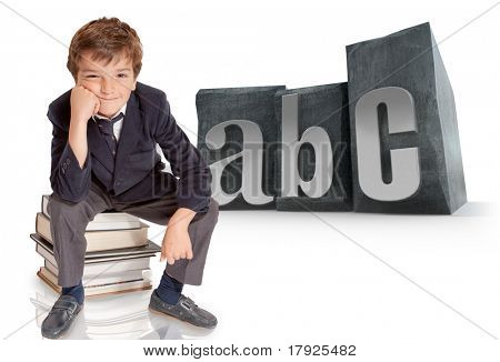 Cute young schoolboy sitting on top of a pile of books with the word ABC on the background