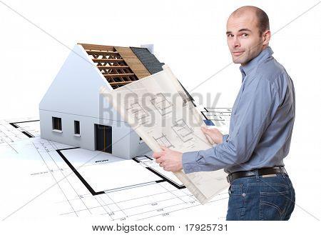 Mann, Pläne und Haus im Bau im Hintergrund hält