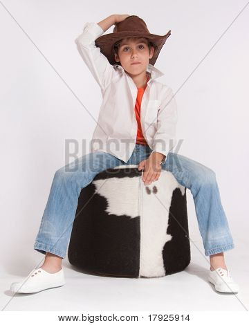 Kid with a cowboy hat riding a cowhide footstool