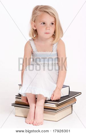 Cute little blonde girl in a nightdress sitting on a pile of books