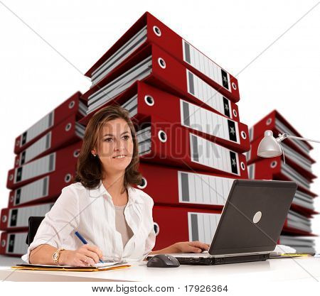 Woman sitting at her desk with piles of ring binders at the background