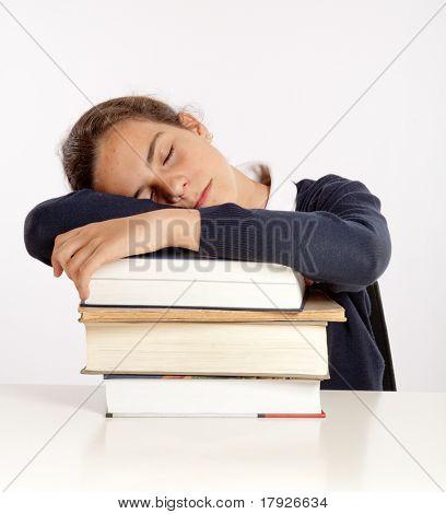 Schoolgirl sleeping on a pile of books