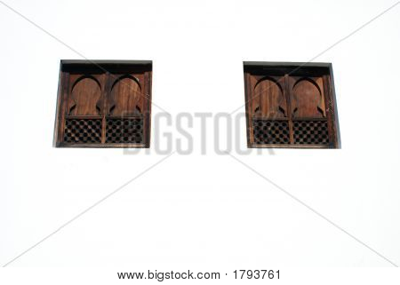Two Small Wood Stained Arabic Style Mosque Windows On White Washed Wall