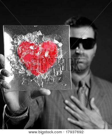 Broken red glass heart businessman metaphor, black background studio shot