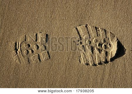 boot shoe footprint over beach warm sand