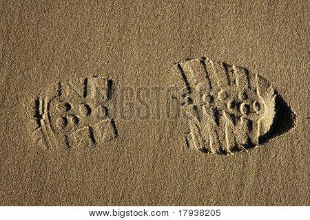 boot shoe footprint over beach warm sand