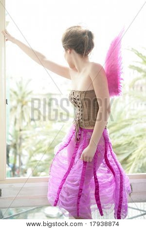 Beautiful redhead woman with pink feather wings on romantic soft light
