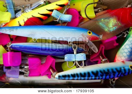 Colorful fishing saltwater fish lures in a box, rusted hooks