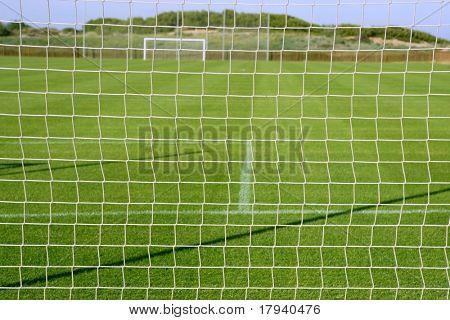 Net soccer goal football green grass field sunny day outdoors