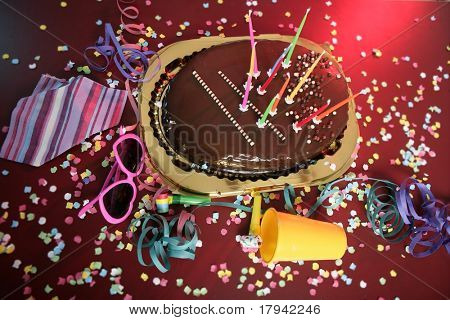 Chocolate holiday party cake on a messy confetti red table