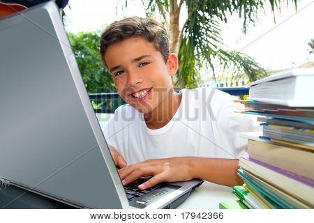 Happy teenager student boy working laptop computer in garden outdoor