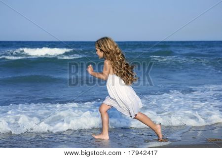 Little girl running beach shore splashing water in blue sea