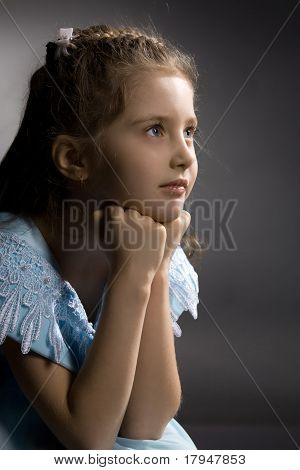 Little pretty thoughtful girl on the arm-chair