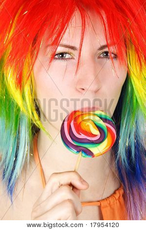 Closeup Of Young Beauty Woman In Multicolored Wig Eating Big Lollipop