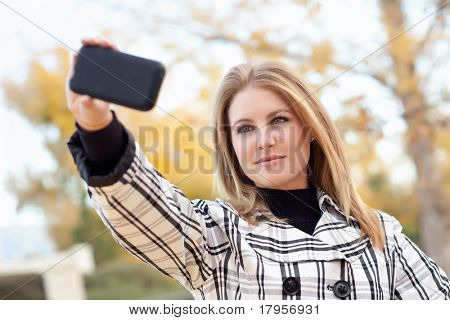 Pretty Young Woman Taking Picture with Camera Phone in the Park One Fall Day.
