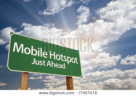 Mobile Hotspot Green Road Sign with Dramatic Clouds, Sun Rays and Sky.