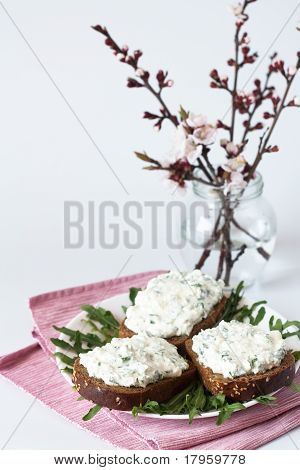 Cheese snack on rye bread, arugula and bouquet of blooming cherry branches