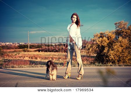young woman with her dog stand on the road, summer day