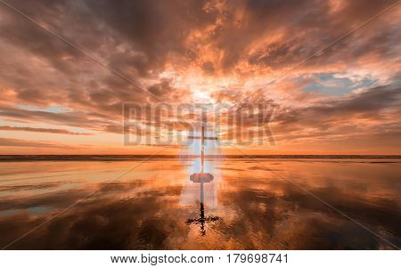 Cross with a image of Jesus Christ on a beach at Sunset.
