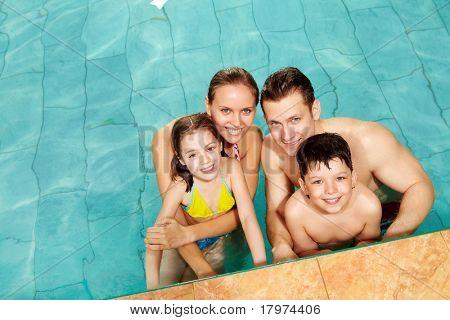 Foto da família feliz na piscina sorrindo para a câmera
