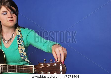 Young Woman Tuning Guitar