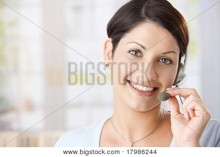 Closeup portrait of happy woman talking on headset, holding on to microphone.
