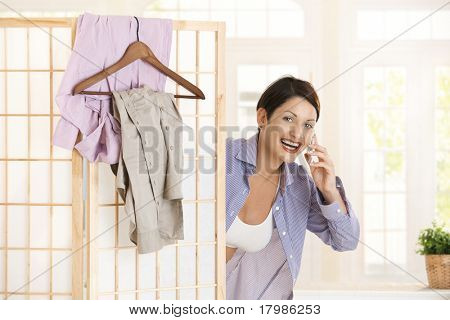 Happy young woman talking on mobile looking out behind dressing panel, smiling.