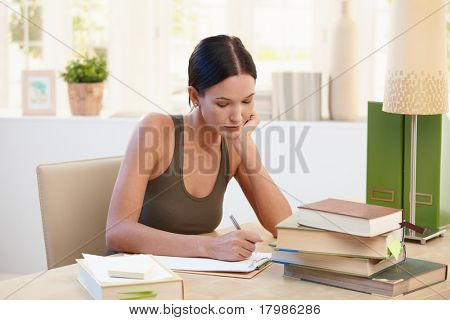 Pretty university student girl studying at home, sitting at desk, writing notes.