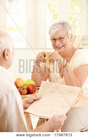 Smiling elderly wife sitting at kitchen table holding coffee mug, looking at camera, husband reading morning papers.