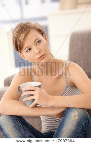 Lässig junge Frau sitzen auf Boden zu Hause denken mit Tee in der hand.