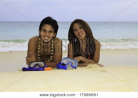 asian couple lounging on the sand